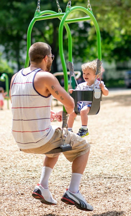 A father and daughter enjoy playing on the swings in the park.