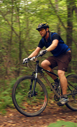 A man pedals his muddy mountain bike on a wooded trail.